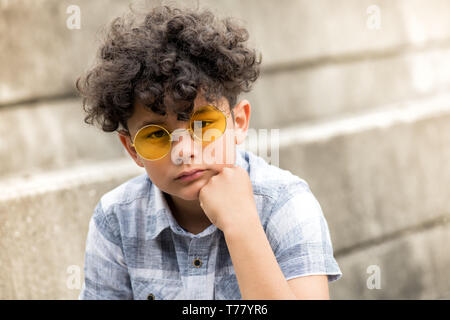 Serious young boy with tousled curly hair sitting on a step outdoors in trendy round yellow sunglasses with chin on hand staring at the camera - Stock Image