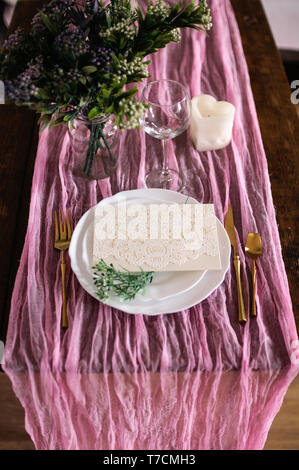 Wooden table is covered with a color runner tablecloth with a white plate and cutlery - Stock Image