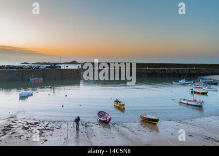 Mousehole, Cornwall, UK. 16th Apr, 2019. UK Weather. After 3 days of gale force winds and heavy rain, the weather has swung round this morning ahead of the Easter weekend. It was calm and mild at sunrise with the promise of a hot day ahead. This photographer was out in the harbour photographing the small fishing boats at sunrise. Credit: Simon Maycock/Alamy Live News - Stock Image