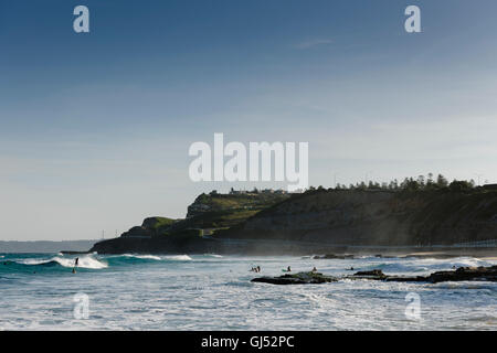 People surfing at Newcastle Beach, New South Wales, Australia. - Stock Image