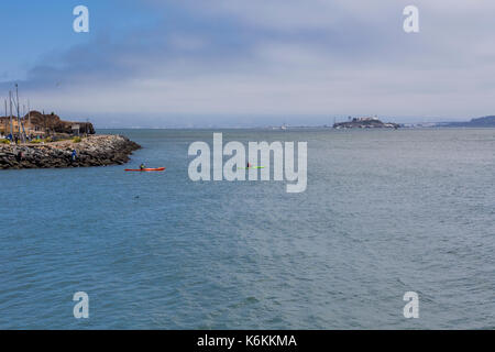 people, adult men, kayakers, kayaking, leaving Fort Baker with view of Alcatraz Prison, Fort Baker, city of Sausalito, Marin County, California - Stock Image