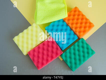 A set of multi-colored sponges and rags for cleaning and cleanliness on a gray background, the concept of outsourcing cleaning company, top View, flat - Stock Image