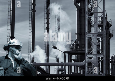 refinery worker with petrochemical industry, smoke and smog - Stock Image