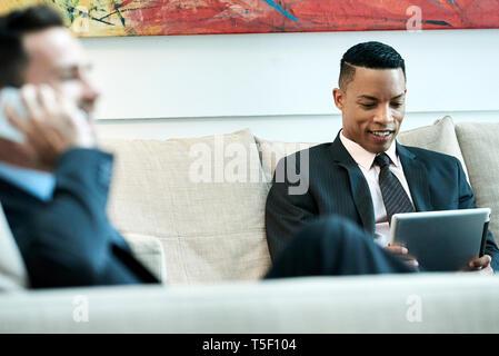 Businessman using digital tablet in hotel lobby - Stock Image