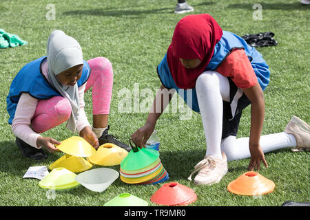 Two girls in Muslim Hijabs prepare to play football on an astroturf training pitch with marker cones. - Stock Image