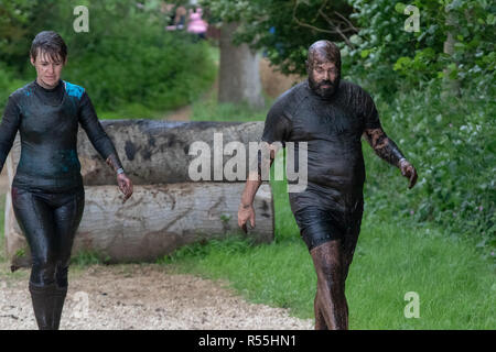 Man and woman covered in mud at a mud run - Stock Image