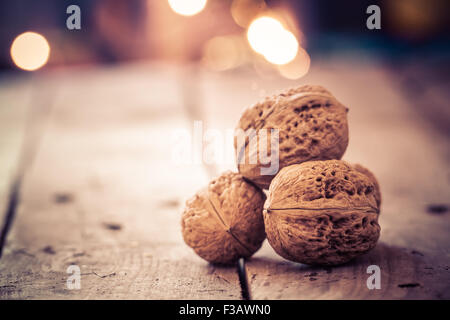 Walnuts on an old wooden table. Christmas background. - Stock Image