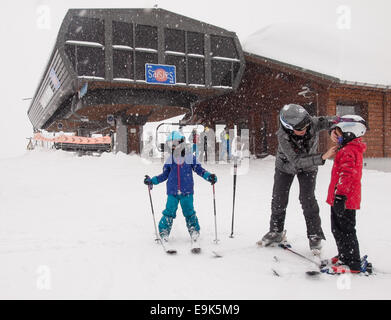woman helping small children prepare to go skiing in front of a ski lift in heavy falling snow - Stock Image
