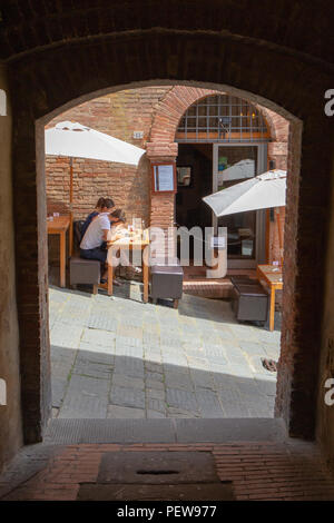 A youg couple is sitting at the terrace of Restaurant & Wine Bar Zest on a steep small street in Siena, Italy - Stock Image