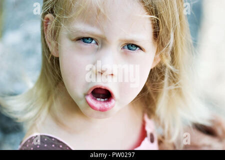Cute blond child angry and throwing a temper tantrum - Stock Image