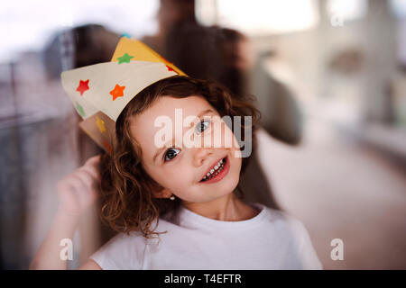 A portrait of small girl with a paper crown at home, looking at camera. Shot through glass. - Stock Image