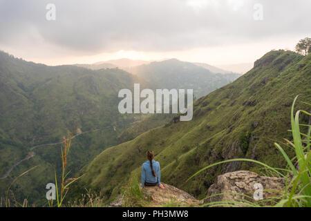 Woman enjoying beautiful view from the top of Small Adams peak. Ella, Sri Lanka. - Stock Image