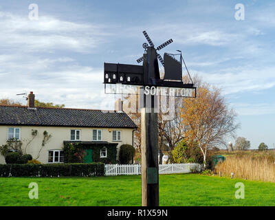 Village sign at West Somerton staithe, Norfolk, celebrating the ancient St Mary's church, the old drainage mill and the wherries built in the village. - Stock Image