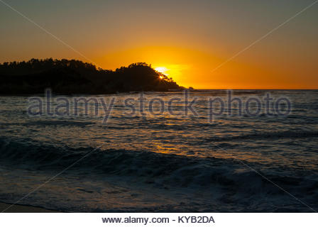 Point Lobos is seen at sunset from Monastery Beach, just south of Carmel, in Monterey County, California. - Stock Image