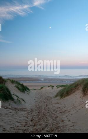 A path between the dunes down to a beach in the early morning - Stock Image