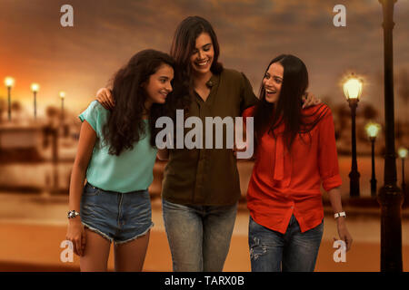 Three girl friends standing outdoors together in evening - Stock Image
