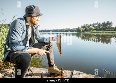 Portrait of a handsome fisherman with fish on the wooden pier near the lake in the morning - Stock Image