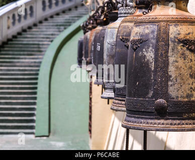 Old traditional prayer bells hanging at the entrance stairway to a temple in Bangkok, Thailand, Asia. - Stock Image