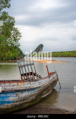 A beached rotting wooden boat in front of the famous Krabi landmarks, Thailand. - Stock Image