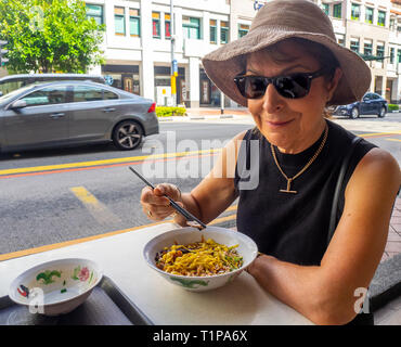 Caucasian female tourist eating traditional Singaporean breakfast bowl of noodles with minced pork and mushrooms al fresco North Bridge Rd Singapore. - Stock Image