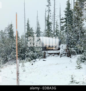 Snow-covered Deschutes National Forest sign with snow marker pole in foreground. Ponderosa pine trees show signs - Stock Image