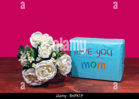 Beautiful bouquet of arranged flowers and a present with a message 'Love You Mom' on a wooden table. mothers day, Easter, valentines, birthday, Christ - Stock Image