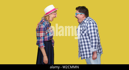 Side view portrait of couple of friends, adult man and woman in casual checkered shirt standing to each other and screaming with opened mouth. Indoor, - Stock Image