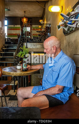 Berlin Prenzlauer Berg. Haliflor Bar & cafe interior. Elderly man drinking beer in quirky pub with period decor - Stock Image