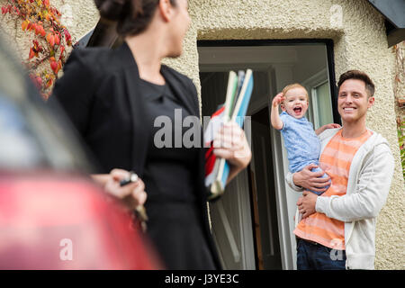 Father and toddler son wave goodbye to mother at front door at home - Stock Image