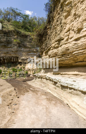 Dry river bed by the cliffs of Ol Njorowa gorge, Hells Gate National Park, Kenya - Stock Image