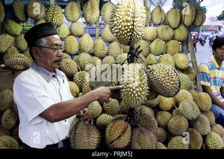 Man selling durian fruit from street stall in Padang, Indonesia - Stock Image