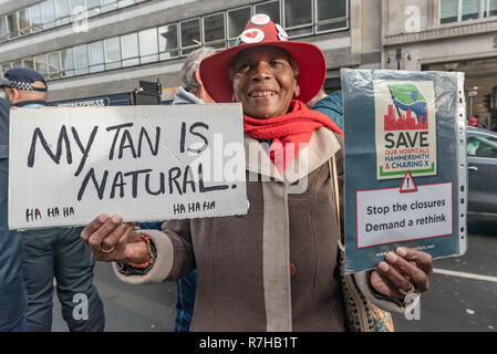 London, UK. 9th Dec, 2018. A protesterhodls a poster 'My Tan is Natural' and another about hospital clousres at the start close to the BBC of the united counter demonstration by anti-fascists marches in opposition to Tommy Robinson's fascist pro-Brexit march. Author Louise Raw at left, Nita Sanghera of UCU at right. The march which included both remain and leave supporting anti-fascists gathered at the BBC to to to a rally at Downing St. Police had issued conditions on both events designed to keep the two groups well apart. Credit: Peter Marshall/Alamy Live News - Stock Image