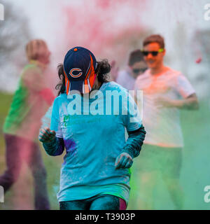 Black female runner with cap looking down and covered in paint on Macmillan cancer charity 5K color fun run. - Stock Image
