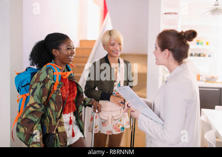 Real estate agent greeting young women friends at house rental - Stock Image