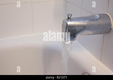 A silver faucet in the bath tub runs water with copy space - Stock Image