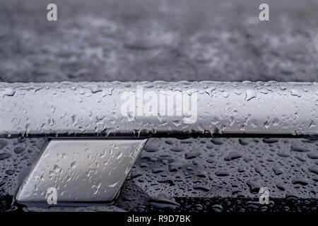 car roof railing abstract closeup with rain drops, T letter shape - Stock Image