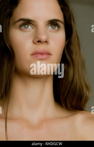 Young woman looking up in thought, portrait - Stock Image