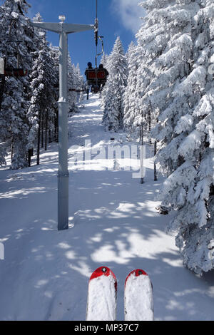 A couple ride the chairlift through a freshly snow landscape. Golte ski resort, Slovenia. - Stock Image