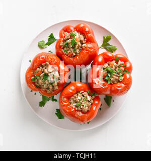Close up of baked stuffed red bell pepper filled with minced meat, rice, onion on white stone background. Top view - Stock Image