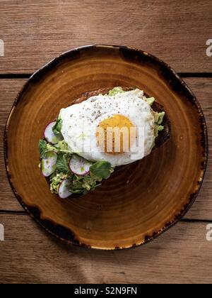 Avocado toast with sunny side up egg on brown plate at breakfast - Stock Image