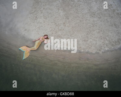 Mermaid laying on a sandbar in Virginia Beach, VA - Stock Image