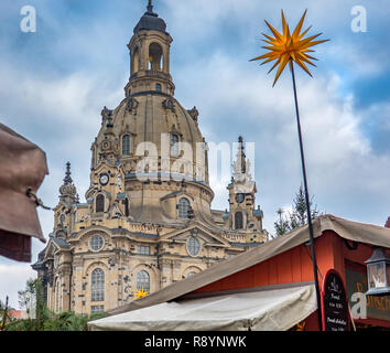 Dresden, Germany, December 14., 2018: The Frauenkirche (church of our lady) behind the Christmas market with a Christmas star and a sales stand in the - Stock Image