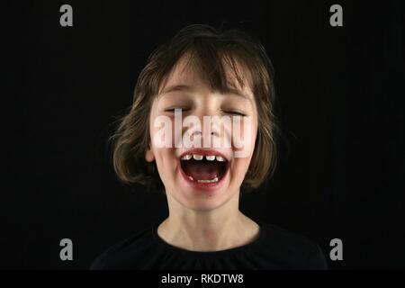 Portrait of a young girl laughing out loud with dimples and her eyes closed against a black background - Stock Image