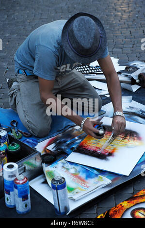 Street male artist creates images of the Roman architecture by using and mixing  aerosol paint in Piazza Navona, a popular square among artists, Rome - Stock Image