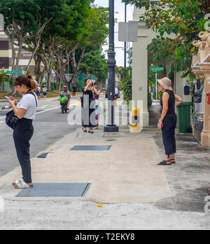 Female tourists and Instagrammers posing on Koon Seng Road, Joo Chiat, Singapore. - Stock Image