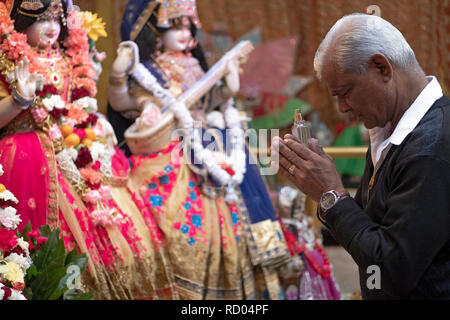 A devout Hindu worshipper with clasped hands & holding a perfume bottle, prays and meditates in front of statues of deities. In Queens, New York. - Stock Image