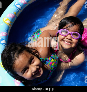 Two girls playing in home pool - Stock Image
