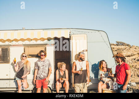 Travelers and alternative people enjoying freedom and desert outdoor - group of friends out of a old caravan for vacation and different life concept.- - Stock Image