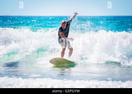 Surfer enjoying high waves in bright sunny day, active lifestyle, extreme water sport, summer time activities - Stock Image