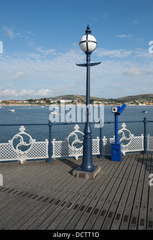 A view across Swanage pier and the bay with a lamppost and blue telescope on the deck - Stock Image